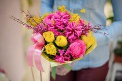 Florist, der einen schönen hellen rosa und gelben Blumenstrauß von Blumen hält Lizenzfreies Stockfoto