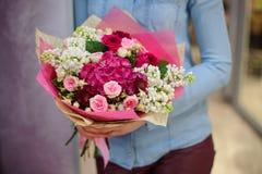 Florist, der einen schönen weißen und rosa Blumenstrauß von Blumen hält Stockbild