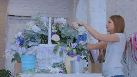 Florist, der großen Blumenkorb mit Blumen am Blumenladen macht stock footage