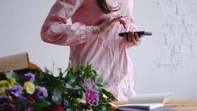 Florist, der am Zähler im Blumenladen, den Preis berechnend steht lizenzfreies stockbild