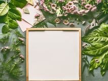 Florist desktop with a lot of decorative fresh green leaves , pink flowers and greeting card mock up around withe tray for florist. Work, top view, flat lay Royalty Free Stock Photography