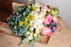 Florist did rich bunch flowers light background, wooden box on surface table. Stock Photography