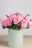 Florist did rich bunch flowers light background, wooden surface. green vase Royalty Free Stock Photography