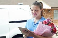 Florist With Digital Tablet, das Hauslieferung vom Blumenstrauß macht Stockfotografie