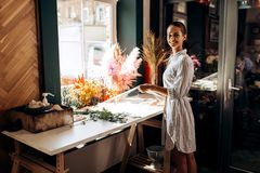 Florist dressed in a striped dress stands near the table with colorful dried flowers and holds transparent packaging royalty free stock image