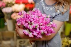 Florist in einem grauen Kleid, das einen schönen zarten rosa Blumenstrauß von Blumen hält Lizenzfreies Stockbild