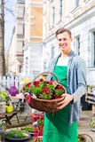 Florist with flower basket at shop selling. Female florist carrying basket with plants in front of flower shop Royalty Free Stock Photography