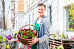 Florist with flower basket at shop selling. Female florist carrying basket with plants in front of flower shop Royalty Free Stock Photo