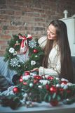 Florist Girl with Christmas Decorations Glass Balls. Evergreen Xmas Tree and Snowflakes Royalty Free Stock Photos
