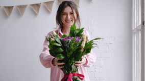 Florist girl looks at the camera and shows the bouquet. Portrait in a flower shop Stock Photography