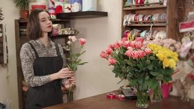 Florist girl is making a floral arrangement from fresh roses in a shop. Floral artist woman is creating a bouquet of beautiful pink rose. She is taking it from stock video footage