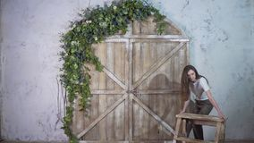 A florist girl moves a small staircase on a beautiful background royalty free stock photo