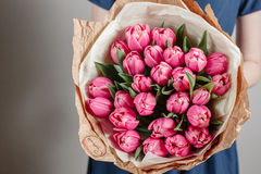 Florist girl with peony flowers or pink tulips Young woman flower bouquet for birthday mother's day. Stock Images