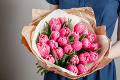 Florist girl with peony flowers or pink tulips Young woman  flower bouquet for birthday  mother's day. Stock Photo