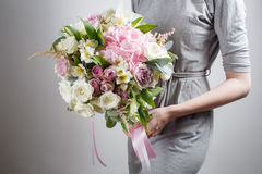 Florist girl with rich bunch flowers. Fresh spring bouquet. Summer Background. Young woman flower for birthday or mother Stock Images