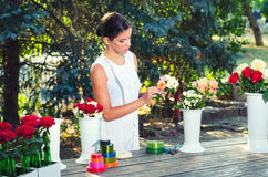 Florist girl in white dress making bouquets of roses on sunny summer day Stock Photo