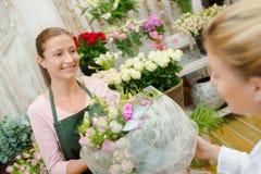 Florist giving arrangement flowers to customer. Florist giving arrangement of flowers to customer Royalty Free Stock Photos
