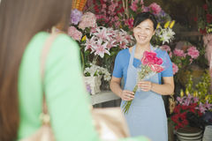 Florist Giving Bunch Of Flowers To Customer Royalty Free Stock Photography