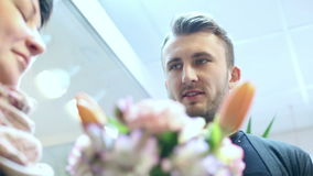 Florist is giving the finished bouquet of flowers to the hands of the customer. stock footage