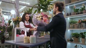 Florist giving ready floral creation to client. Cheerful attractive female floral artist giving gorgeous flower arrangement to satisfied customer with good stock video footage
