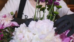 Florist hand make bouquets flowers in grey pot stock video footage