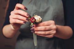 Florist hands creating flower decoration closeup. Stock Photo
