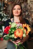Florist hands holding bouquet flowers closeup. Stock Images