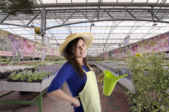 Florist with hat in greenhouse Royalty Free Stock Image