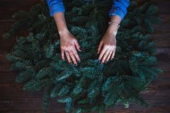 Florist and her hands on a fir branches start to prepare christmas wreath Royalty Free Stock Photos