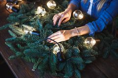 Florist and her hands on a fir branches start to prepare christmas wreath Stock Photo