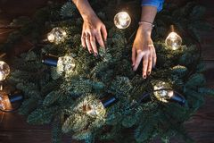 Florist and her hands on a fir branches start to prepare christmas wreath Royalty Free Stock Images