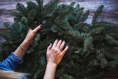 Florist and her hands on a fir branches start to prepare christmas wreath Royalty Free Stock Image