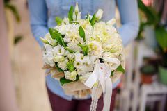Florist holding a beautiful white wedding bouquet of flowers. On the blurred background. Bouquet concept Royalty Free Stock Images