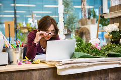 Florist Holding Glasses While Using Laptop In Royalty Free Stock Photo
