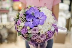 Florist holding tender flower composition in blue, white and purple tones consisting of roses and other beautiful flowers. Florist holding a tender flower stock photo