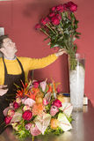 Florist just finishing rich flower arrangement Royalty Free Stock Photos