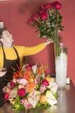 Florist just finishing rich flower arrangement royalty free stock photos