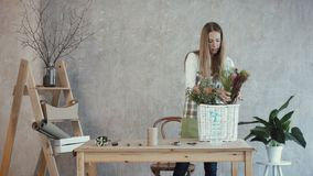 Florist laying out flowers and plants at workplace. Charming female florist in apron laiyng out fresh flowers and plants at her workplace. Elegant professional stock video footage