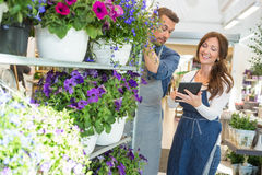 Florist Looking At Female Colleague Using Tablet. Male florist looking at female colleague using tablet computer in flower shop Royalty Free Stock Photography