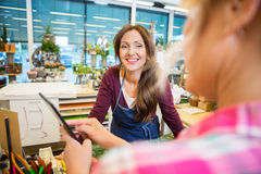 Florist Looking At Female Customer Using Digital Royalty Free Stock Photography