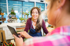 Florist Looking At Female Customer Using Digital Royalty Free Stock Images