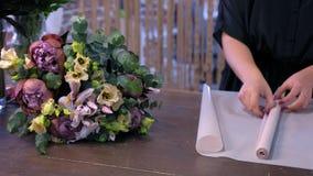Florist makes flower bouquet prepares paper to packaging in shop, hands closeup.