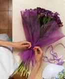 Florist making  bouquet of purple flowers Stock Images