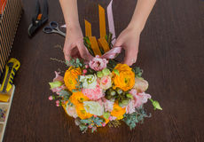 Florist making bright orange and pink bouquet Royalty Free Stock Photo