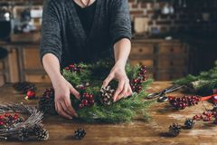 Florist making Christmas fir wreath. Cropped view of florist making Christmas wreath of fir branches, decorative berries and pine cones at workplace royalty free stock images