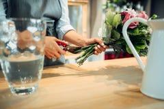 Florist making flowers arrangement in shop stock photography