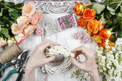 Florist making wicker wreath decorated with tiny daisies Stock Photo