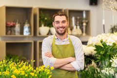 Florist man or seller at flower shop counter. Sale, small business and floristry concept - happy smiling florist man or seller at flower shop royalty free stock photo