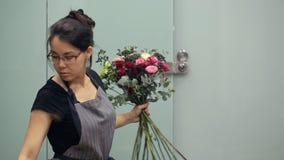 Florist mit aller Konzentration sammelt Blumen im Blumenstrauß stock footage