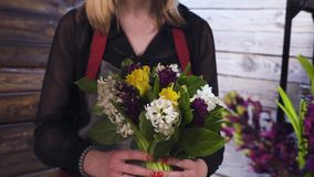 Florist in own flower shop, preparing bouquets stock video